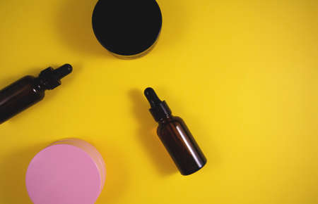 Cosmetic containers jar of cream and bottle of serum on yellow background. Flat lay, top view and copy space