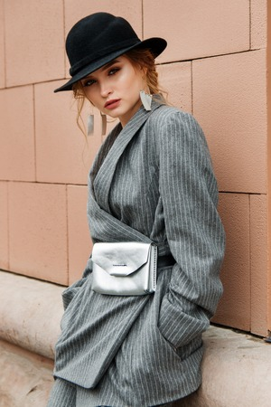 young stylish beautiful woman fashion model is posing in street, wearing pantsuit, having purse on her waist