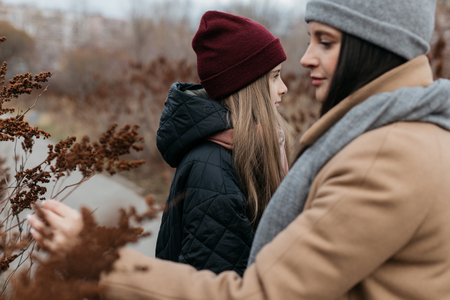 Mother and doughter teenager are walking on the street in warm autumn clothes