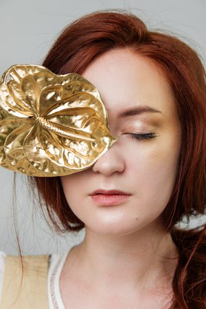 young beautiful woman has red hair creative gold make up are posing in a studio with flowers