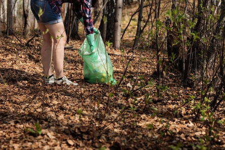 woman picking up dump on dirty forest