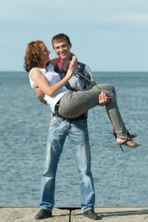 man is holding his wife on hands outdoors at sea  photo