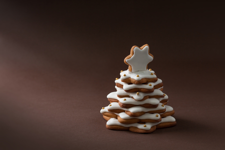 spice cake: christmas spice cake in the form of fir on the brown background Stock Photo