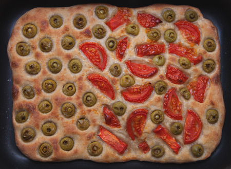 homemade bread focaccia with tomatoes and olives, horizontal photo