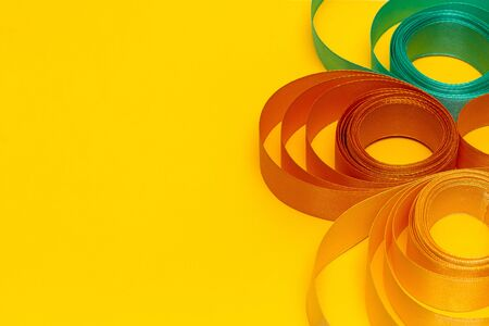 gold, green, white, beige swirled ribbon on yellow background, top view, texture, background, bright, copy space