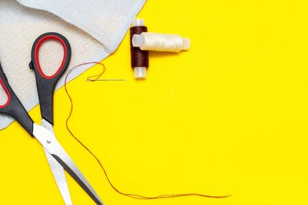 fabric, brown and beige thread, needle, scissors on a yellow Sunny background, top view, place for text, copyspace Stockfoto