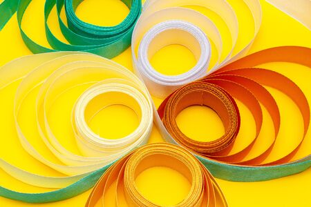 gold, green, white, beige swirled ribbon on yellow background, top view, texture, background, bright