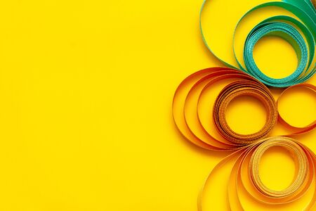 multi-colored swirled ribbon on yellow background, top view, texture