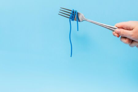 wires wound around a fork like noodles on a blue background