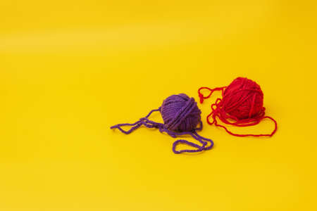 a tangles of red and blue woolen threads lies unraveled on a yellow background. the view from the top Stok Fotoğraf