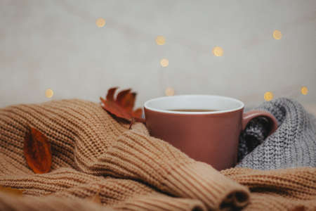 on the table are two cozy sweaters rolled up around a hot cup of coffee, autumn dry leaves are scattered nearby and a garland of small lights is lying, Flatley, side view