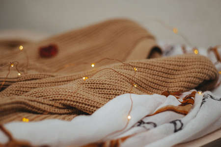 a beige woolen knit sweater and a light brown cotton scarf lie on the table. On top is an led garland. side view
