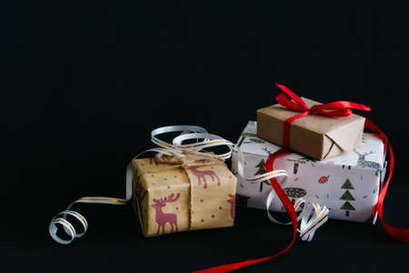 gift boxes Packed in wrapping paper and tied with ribbons for the new year or Christmas lie in a pile on a black background