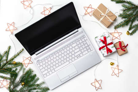 Christmas online shopping. An open laptop on a white background, gift boxes tied with a red ribbon, green fir branches, garlands of stars. Online trading during the winter holidays.
