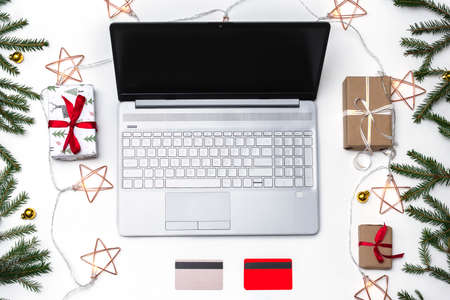 Christmas online shopping. An open laptop on a white background, a credit card, gift boxes tied with a red ribbon, green fir branches, garlands of stars. Online trading during the winter holidays. 版權商用圖片