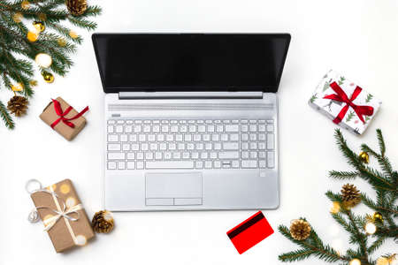 Christmas online shopping. An open laptop on a white background, a credit card, gift boxes tied with a red ribbon, green fir branches, garlands of stars. Online trading during the winter holidays. Stock fotó
