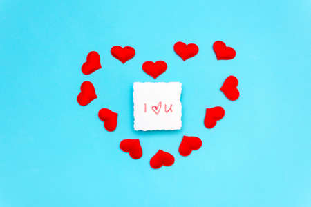 a note on which is written a declaration of love in lipstick, lies on a blue background, surrounded by red hearts in the shape of a heart. Minimal Valentine's Day greeting card with copy space.