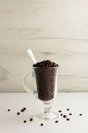 A glass mug is full of coffee beans on a light background
