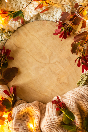 Wooden background with red leaves and a dais on the wooden background. Concept of the autumn. View from above. place for text