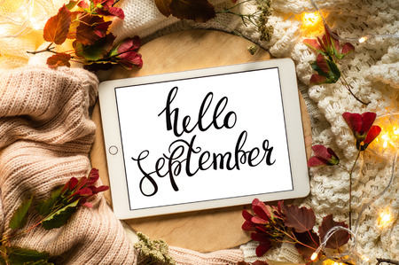 The tablet says the word hello September with red leaves and a dais on the wooden background. Concept of the autumn View from above. Copy Space.