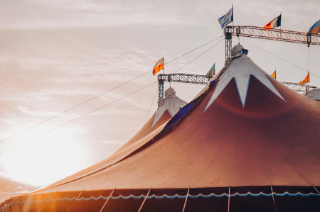 Circus tent under a warn sunset and chaotic sky without the name of the circus company. A fragment of the circus design, a dome on the sky background. A circus on wheels.