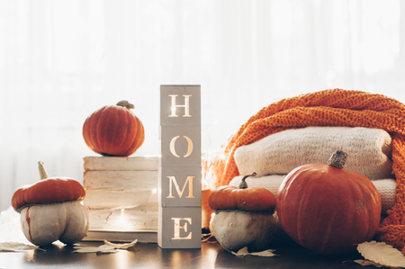 Background with warm sweaters and the inscription HOME. Pile of knitted clothes with autumn leaves, warm background, pumpkins, autumn flowers, knitwear, Warmth, coziness. Autumn concept.