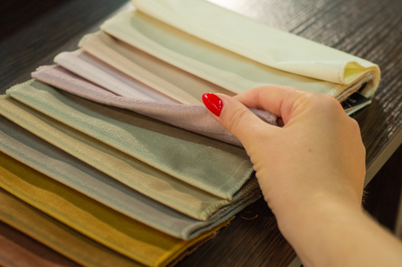 The girl is viewing samples of fabric for furniture in home or commercial building. Large color catalog of fabric. Design. Consultation