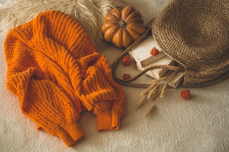Cozy knitted warm orange sweater with old books and vintage straw bag on white warm plaid with pumpkin, physalis, Autumn books and reading. autumn mood. Autumn Winter time.