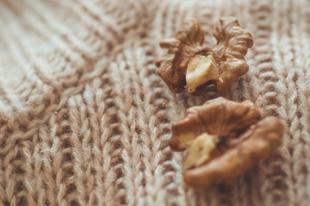 Walnuts in sweaters. Walnut kernels in a bowl and whole walnuts. Cozy autumn or winter concept.