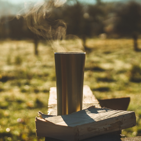 Breakfast with a book in the open air, warm blanket, Steam over a thermo cup. Open book on nature. Book and drinking coffee. Reading at outdoor