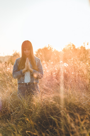 girl closed her eyes, praying outdoors, Hands folded in prayer concept for faith, spirituality and religion. Peace, hope, dreams concept.