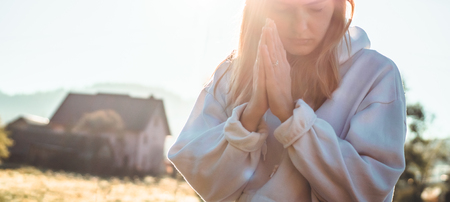 In the morning Girl closed her eyes, praying outdoors, Hands folded in prayer concept for faith, spirituality and religion. Peace, hope, dreams concept.