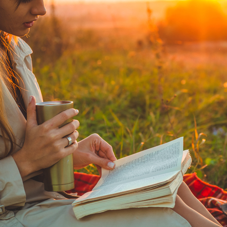 The concept of lifestyle and family outdoor recreation in autumn. Girl with hat read books on plaid with a thermo cup. Autumn. Sunset. Cozy 스톡 콘텐츠 - 111463786