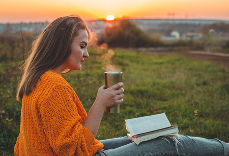 The concept of lifestyle and family outdoor recreation in autumn. Girl read books on plaid with a thermo cup. Autumn. Sunset. Cozy