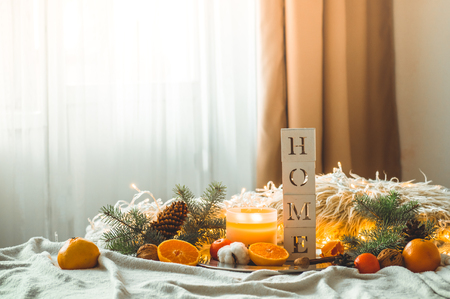 Cozy winter morning  home. The word HOME and Tangerines in a winter composition, Christmas trees, candles, cones, cotton. Warm pillows and garlands on the background. Symbol of New Year and Christmas