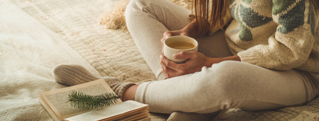 Cozy home. Beautiful girl is reading a book on the bed. Good morning with tea and book. Pretty young girl relaxing. The concept of reading
