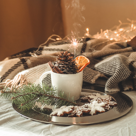 cup with cones and dry orange with sparkler, fir branch, Christmas cookies, cozy knitted blanket. Winter, New Year, Christmas still life.