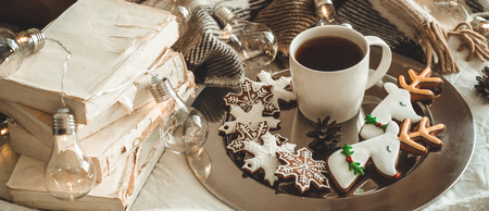 cup with tea or coffee, fir branch, Christmas cookies in the shape of snowflakes, cozy knitted blanket, cotton and cozy garland. Winter, New Year, Christmas still life.
