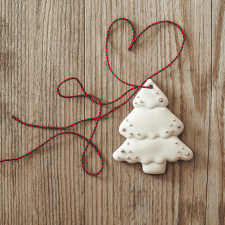 Gingerbread christmas tree hanging over wooden background with heart Stock Photo