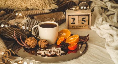 Christmas still life. Old vintage wooden calendar set on the 25 of December with cup with tea or coffee, cookies in the shape of snowflakes, oranges with christmas decorations and nuts