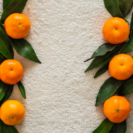 Tangerines (oranges, mandarins, clementines, citrus fruits) with leaves   ,  background, copy space. Stock fotó