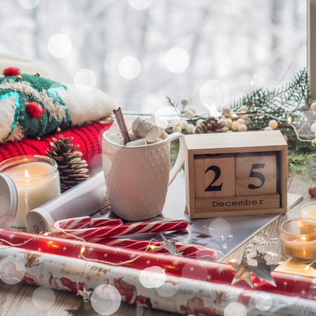 25 December Calendar. Christmas decor: Warm sweater, cup of hot cocoa with marshmallow and led string lights, candy, candles and Christmas tree. Winter mood, holiday decoration.