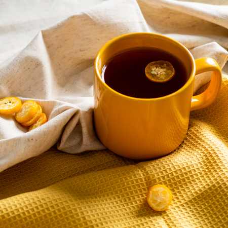 Cup with tea kumquat on yellow background Stock Photo