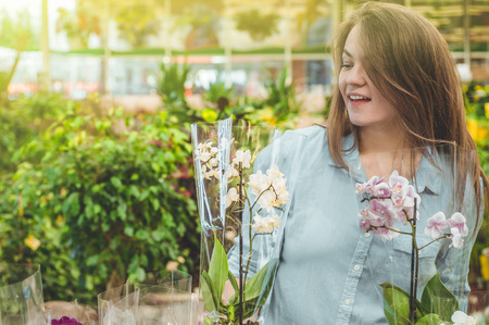 Beautiful female customer smelling colorful blooming orchids in the retail store. Gardening In Greenhouse. Botanical garden, flower farming, horticultural industry concept Stock Photo