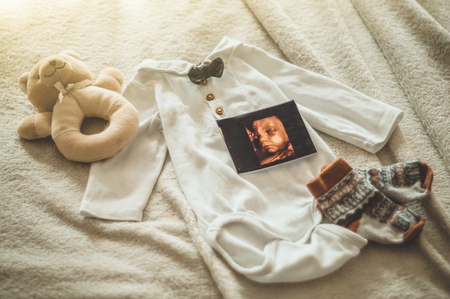 Little hand made baby clothes. Photo of ultrasound. newborn clothes on beige woolen background. Unity, protection and happiness