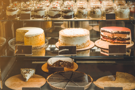 Many delicious cakes in the shop window of a cozy cafe. Tasty sweets. Imagens