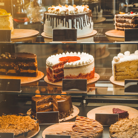 Many delicious cakes in the shop window of a cozy cafe. Tasty sweets.