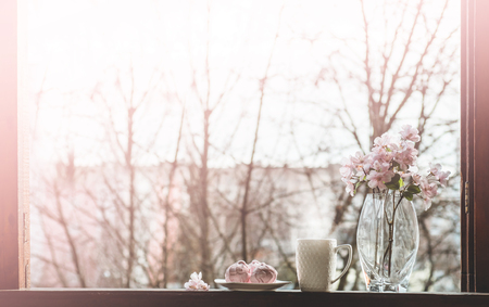 Cozy spring still life: cup of hot tea with spring bouquet of flowers on vintage windowsill with a pink marshmallow. Spring. Apartment.