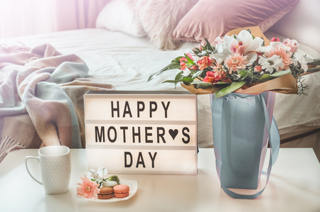 Happy mothers day. A beautiful bouquet of flowers with hot tea on the table. Breakfast in bed on Mothers day.