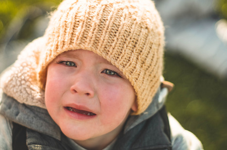 Crying little boy. Cry. Portrait of boy. Caucasian child looks at camera. Charming boy the kid cries with tears in his eyes.
